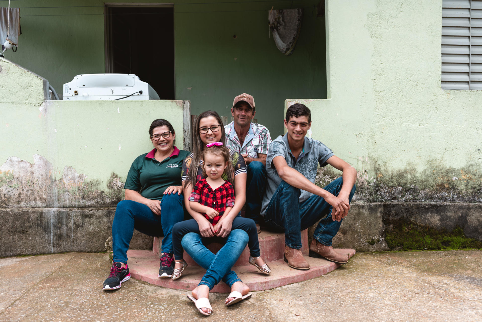 Family sitting in front of their house